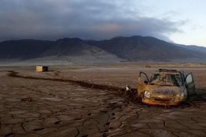 A vehicle partially submerged in dry mud is pictured in an area that was hit by floods at Chanaral town